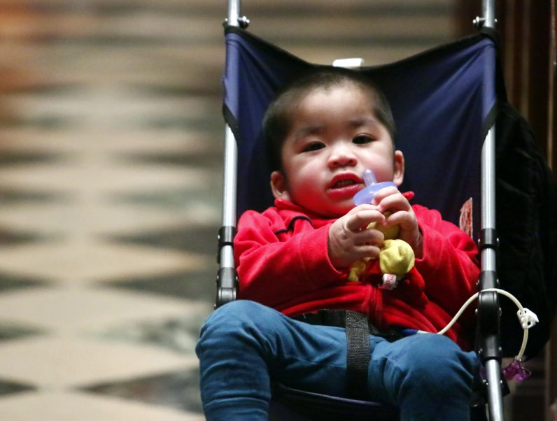 Huy Tran-Phan happily attends the Mass of the Lord's Supper with his parents on Holy Thursday, April 12.