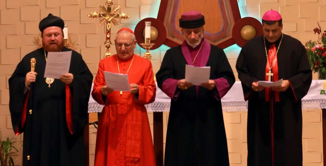 Chaldean Catholic Patriarch Louis Sako of Baghdad, Iraq, in red, leads a 2016 prayer service with other religious leaders  at the Church of our Lady of Perpetual Help in in Ainkawa, Iraq. The patriarch is supporting a more than 80-mile peace march during Holy Week. (CNS photo/Amel Pain, EPA)