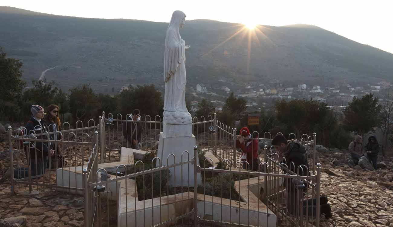 Pilgrims pray around a statue of Mary on Apparition Hill in Medjugorje, Bosnia-Herzegovina, in this Feb. 26, 2011, file photo. Pope Francis has appointed Archbishop Henryk Hoser of Warsaw-Praga, Poland, as his special envoy to Medjugorje, the site of alleged Marian apparitions. A Vatican statement said his role would be to study the pastoral situation in Medjugorje. (CNS photo/Paul Haring)