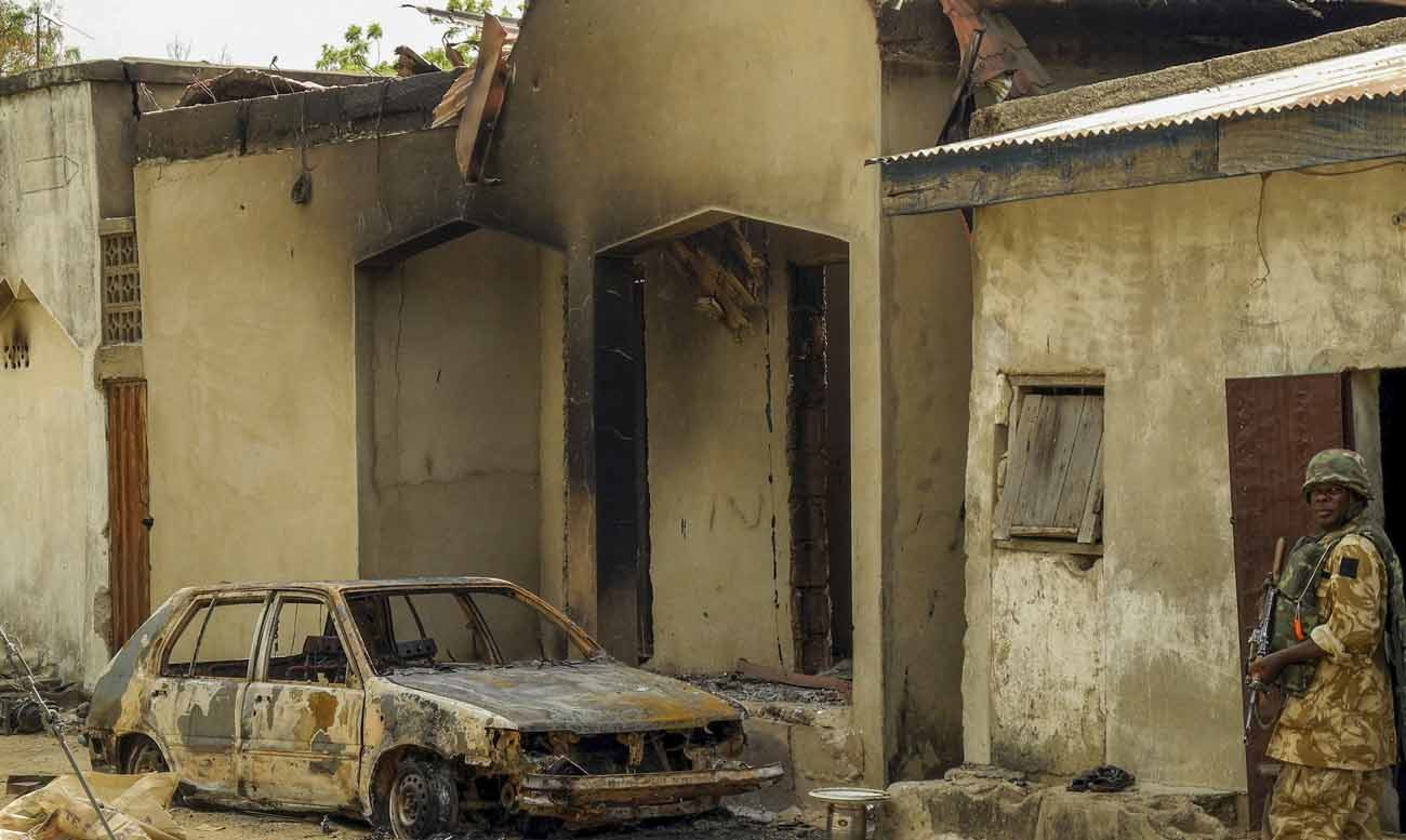 A Nigerian soldier walks near a building and vehicle destroyed by Boko Haram Islamic militants in 2015 after Nigerian troops recaptured Gwoza. (CNS photo/EPA)
