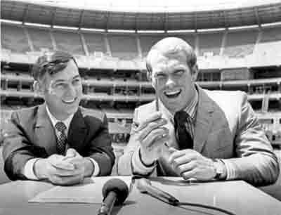Dan Rooney, then vice president of the Pittsburgh Steelers, smiles as quarterback Terry Bradshaw holds up the pen he just used to sign his first contract with the Steelers in 1970.  (CNS photo/Jerry Siskind, Reuters)