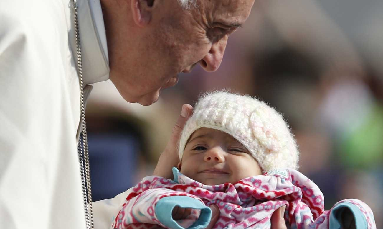 Pope Francis greets a baby during his general audience in St. Peter's Square at the Vatican April 12. (CNS photo/Paul Haring)