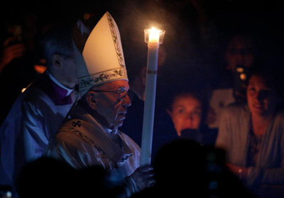 Pope Francis carries a candle as he arrives to celebrate the Easter Vigil in St. Peter's Basilica at the Vatican April 15. (CNS photo/Paul Haring)