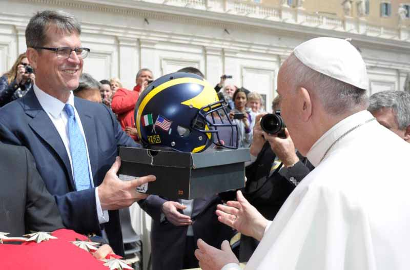 Jim Harbaugh, head football coach for the University of Michigan, presents Pope Francis with a team football helmet during the pope's general audience in St. Peter's Square at the Vatican April 26. (CNS photo/L'Osservatore Romano)