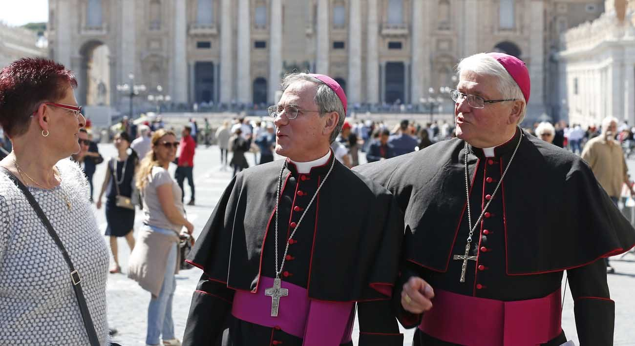"Bishops Ronald P. Fabbro of London, Ontario, and Douglas Crosby of Hamilton, Ontario, chat with a tourist after posing for a photo in front of St. Peter's Basilica during their ""ad limina"" visits to the Vatican April 25. (CNS photo/Paul Haring)"