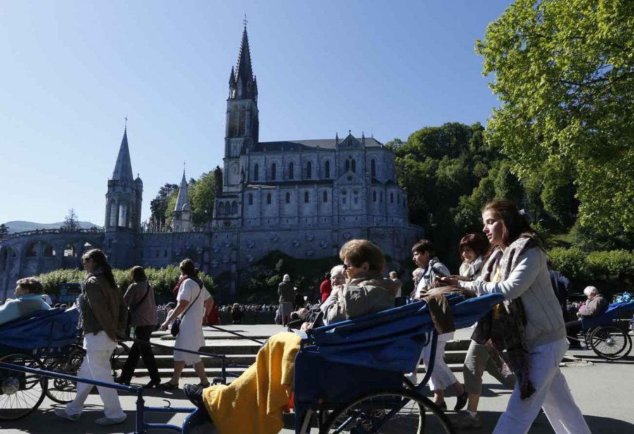 Caregivers push pilgrims in wheelchairs in 2014 at the Shrine of Our Lady of Lourdes in France. (CNS photo/Paul Haring)