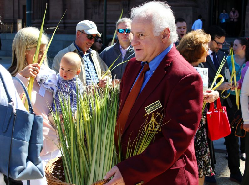 A greeter for the cathedral hands out palm before the start of the outdoor procession.