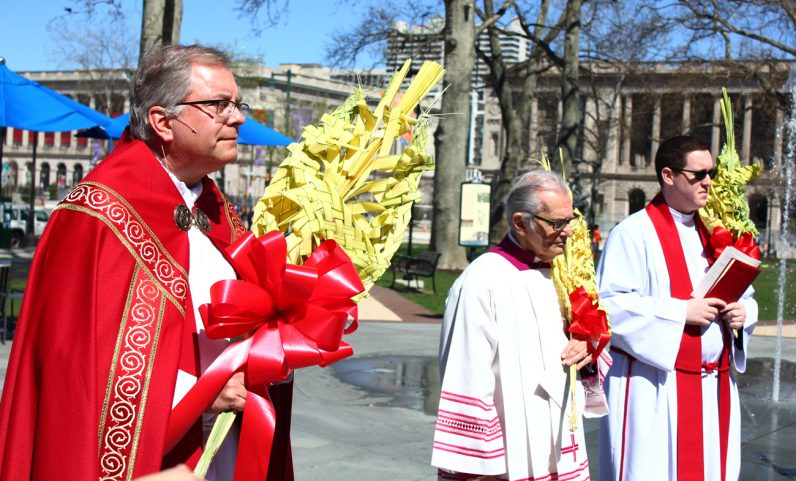 From left, Father Dennis Gill, Msgr. Louis D'Addezio and Father Kenneth Brabazon carry beautifully woven palm on Palm Sunday, April 9.