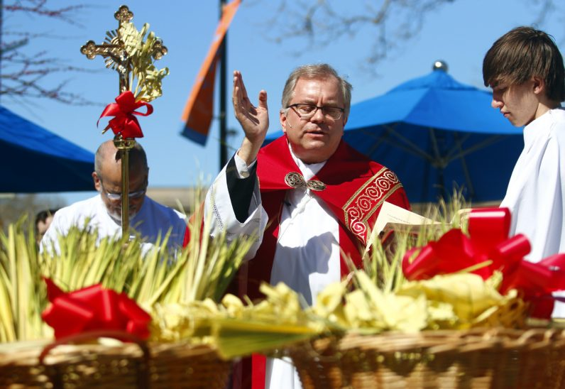 Father Dennis Gill blesses palm in Sister Cities Park across from the Cathedral Basilica of SS. Peter and Paul during the solemn Mass on Palm Sunday, April 9.