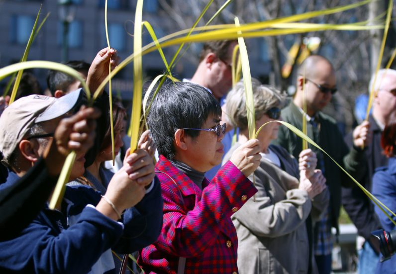 Agnes Su holds and other faithful hold up their palm fronds to be blessed on Palm Sunday.