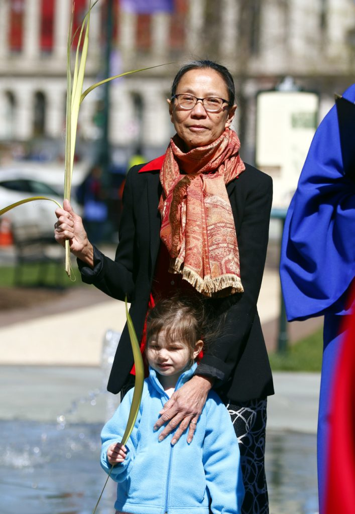 Maria Erdosy and her granddaughter Charolette hold their palms for blessing in Sister Cities Park across from the cathedral where Palm Sunday Mass began on April 9.