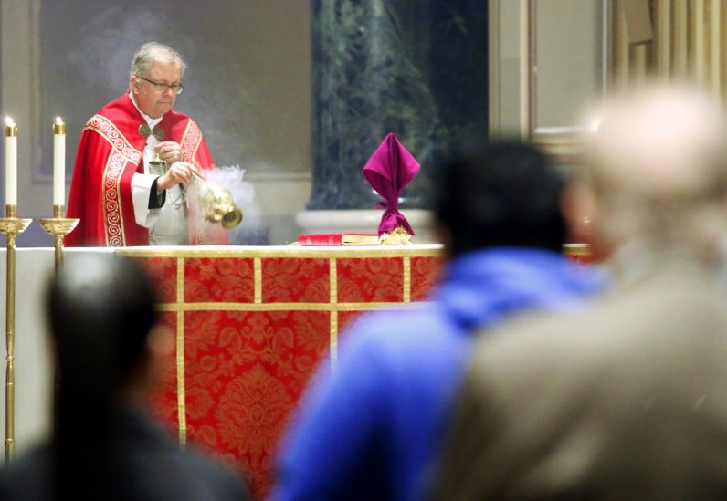 Father Dennis Gill incenses the altar at the cathedral on Palm Sunday, April 9.