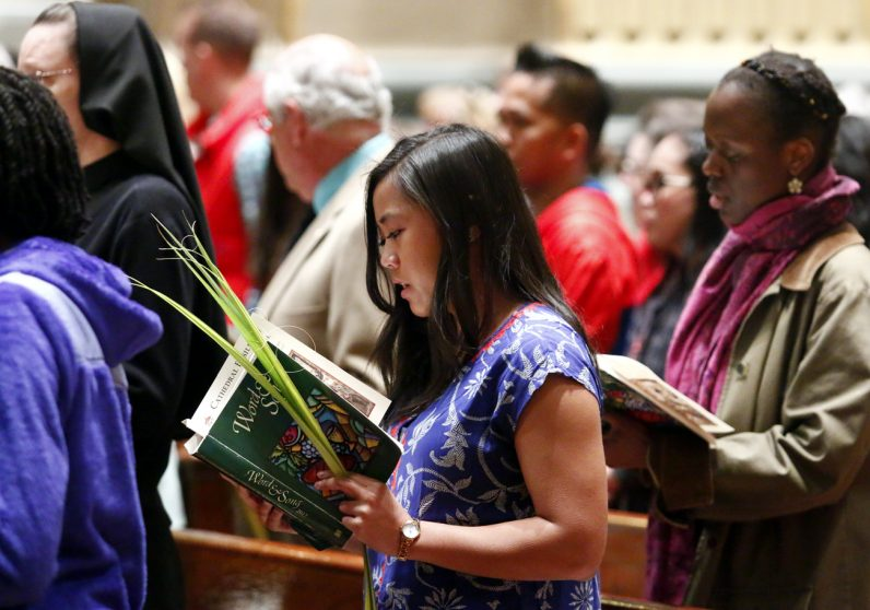 Abby Cabrera holds her palm as she participates in the Gospel proclamation of the passion of Jesus at Palm Sunday Mass at the Cathedral Basilica of SS. Peter and Paul.