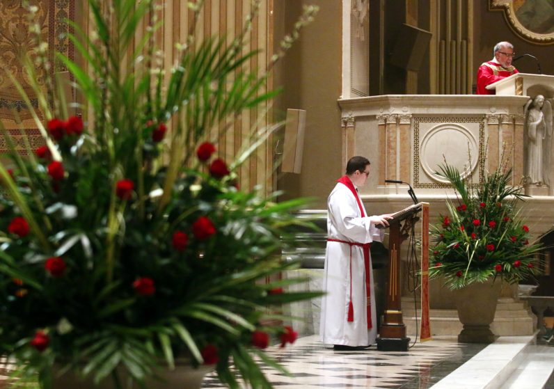 Father Kenneth Brabazon  (left), Deacon Epifanio DeJesus (in pulpit) and Father Dennis Gill (not shown) proclaim the Gospel on Palm Sunday at the Cathedral Basilica of SS. Peter and Paul.