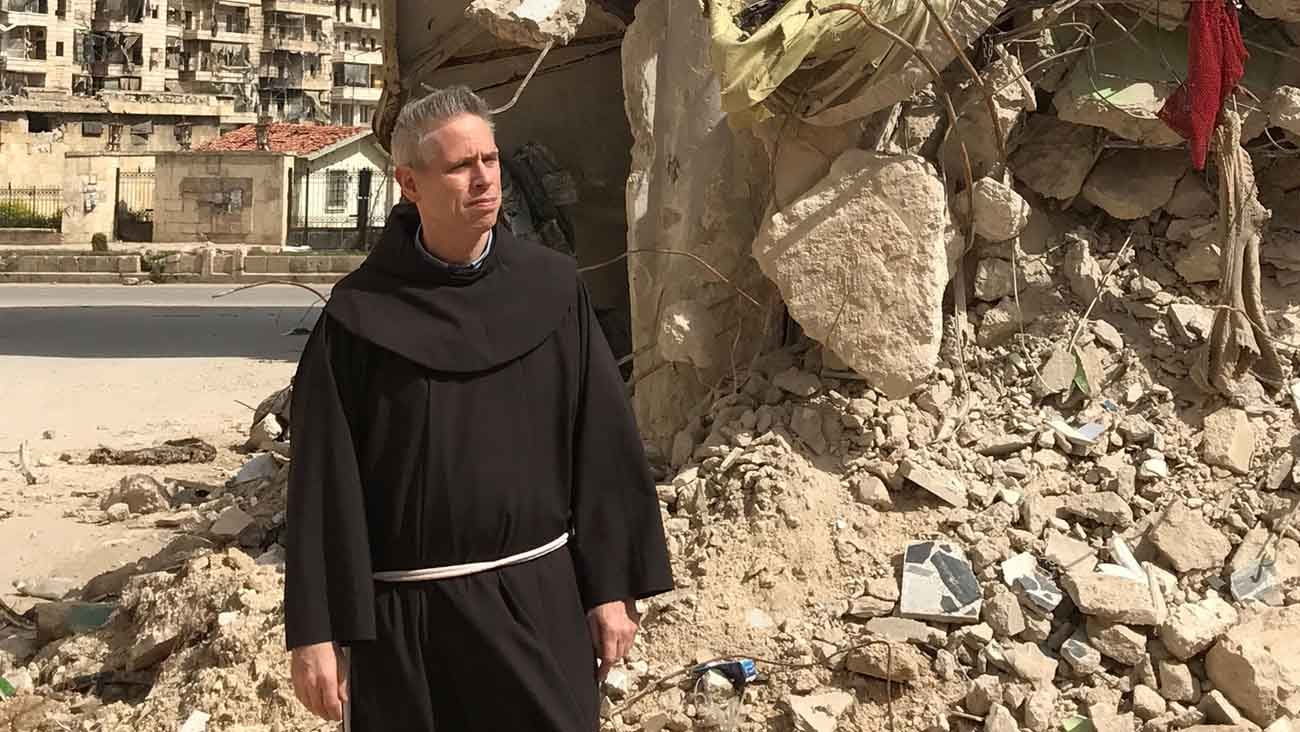 Father Michael Perry, minister general of the Franciscans, walks past the rubble of a bombarded building in Aleppo, Syria, during an early April visit to Franciscan friars there. (CNS photo/courtesy of the Franciscan Generalate)