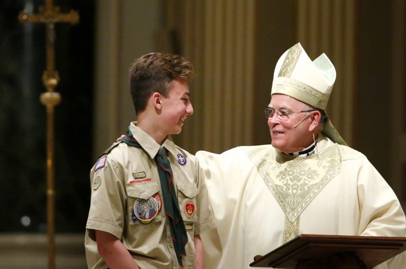 Cody Kulik from Troop 34 at St. Jude Church, Chalfont, helps Archbishop Charles Chaput with his homily during the scout Mass.