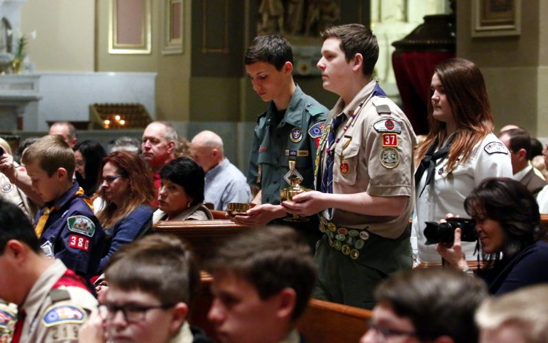 Boys and a girl active in Catholic Scouting bring up the offertory gifts during Mass.