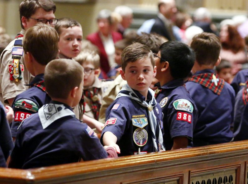 Young men offer one another a sign of peace during the annual Scout Mass.