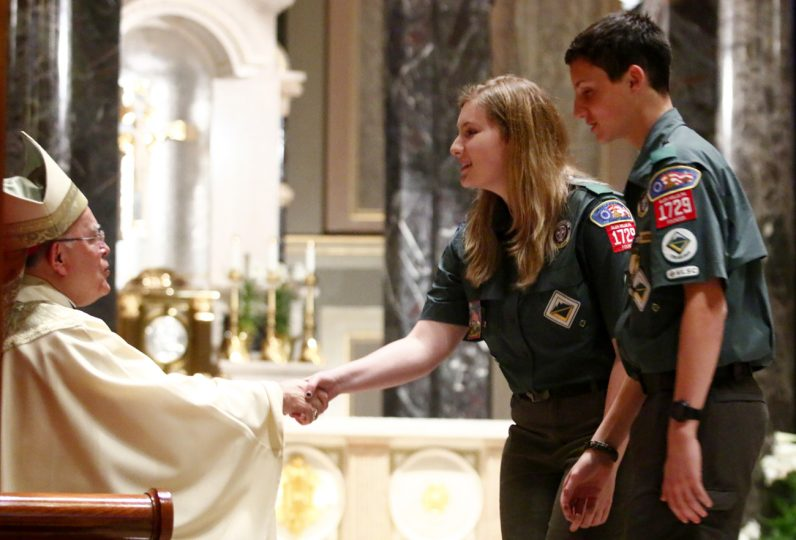 Archbishop Charles Chaput congratulates siblings Emma and Clayton Bromley from Crew 1729 at St. Thomas the Apostle Parish, Chester Heights, as they are awarded the Pope Pius XII Emblem.