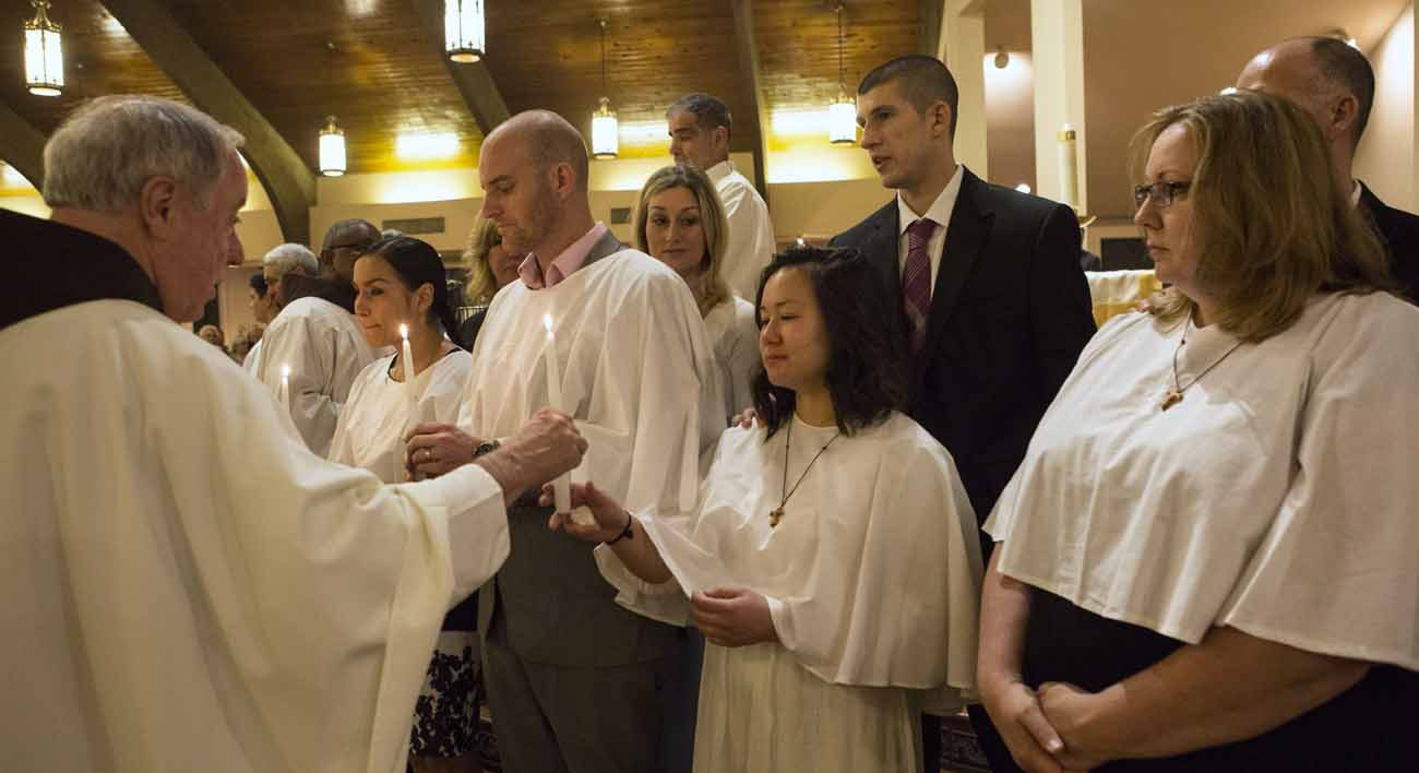 The newly baptized receive their baptismal candles during the Easter Vigil April 16 at St. Francis of Assisi Church in Triangle Va. Thousands of new Catholics joined the Catholic Church during the Easter Vigil at churches around the U.S. (CNS photo/Octavio Duran)