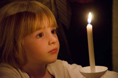 A girl is enamored of her Easter candle during the Easter Vigil April 15 in the Cathedral of the Immaculate Conception in Wichita, Kan. (CNS photo/Christopher Riggs, The Catholic Advance)
