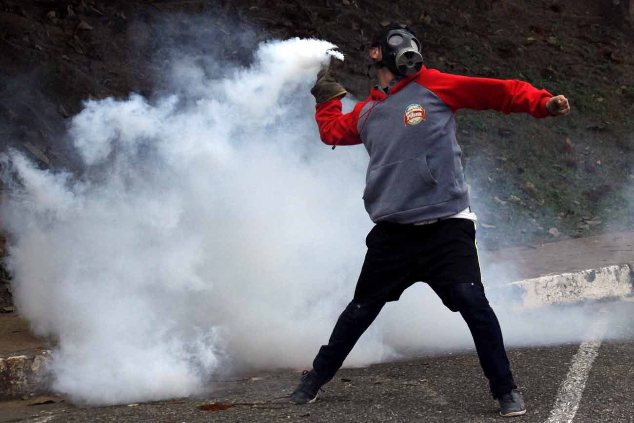 """A demonstrator throws a tear gas canister back at police during an April 5 protest in San Cristobal, Venezuela. The nation's bishops have called for """"peaceful civil disobedience"""" to restore constitutional order. (CNS photo/Carlos Eduardo Ramirez, Reuters)"""