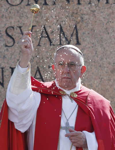 Pope Francis blesses with holy water as he leads a service at the obelisk at the beginning of Palm Sunday Mass in St. Peter's Square at the Vatican March 20. (CNS photo/Paul Haring) See POPE-PALM-SUNDAY March 20, 2016.