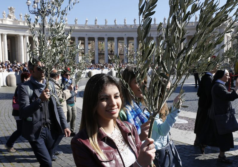 People carry palm fronds in procession as Pope Francis celebrates Palm Sunday Mass in St. Peter's Square at the Vatican April 9. (CNS photo/Paul Haring)