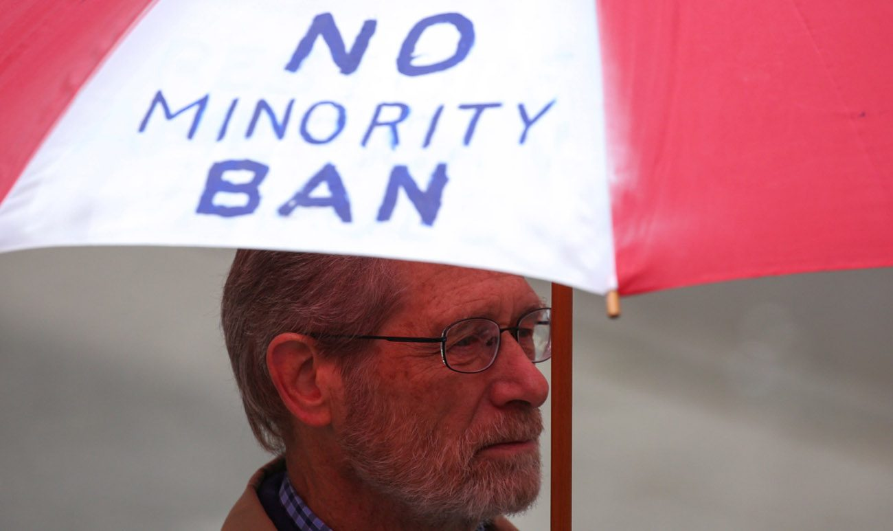 A man holds an umbrella during a protest in Seattle May 15 against President Donald Trump's travel ban. The U.S. Court of Appeals for the 4th Circuit, based in Virginia, issued a 10-3 ruling May 25 to uphold a Maryland federal court's injunction against the temporary ban. (CNS photo/David Ryder, Reuters)