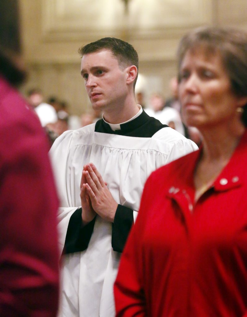 Newly conferred acolyte David O'Brien prays during Mass.