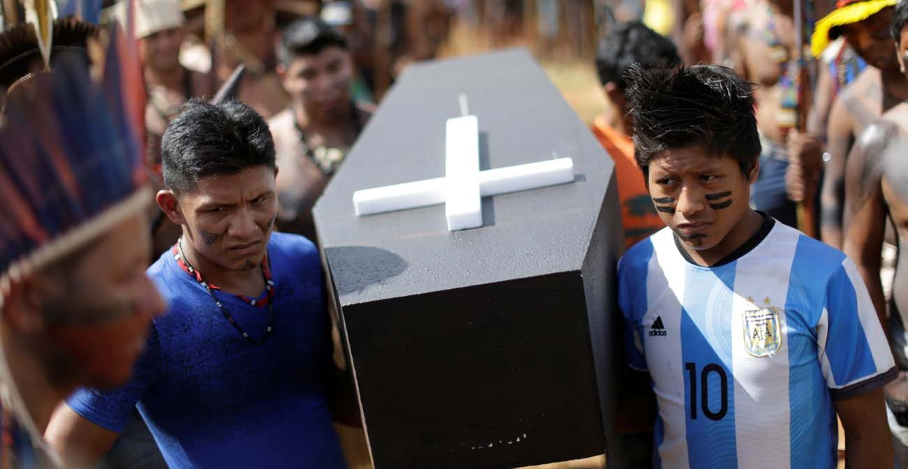 Brazilian Indians in Brasilia carry a symbolic coffin April 25 to show the death of indigenous rights in their country. The Brazilian bishops' Indigenous Missionary Council criticized an April 30 attack in a remote area of Maranhao state that left 13 Gamela Indians injured. (CNS photo/Ueslei Marcelino, Reuters)