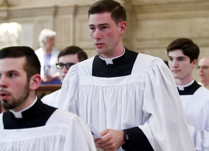 Fourth College graduate Michael Bollinger, center, joins his classmates in procession in St. Martin's Chapel at the seminary.