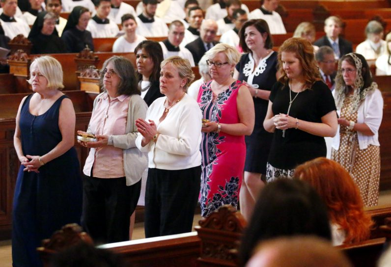 The mothers of the graduates bring up the offertory gifts for Mass at St. Charles Seminary.