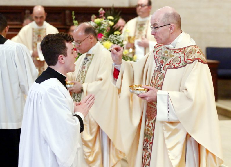 Philadelphia seminarian Eric Tamney receives Communion from Bishop Timothy Senior at the baccalaureate Mass May 16 in at St. Charles Borromeo Seminary.