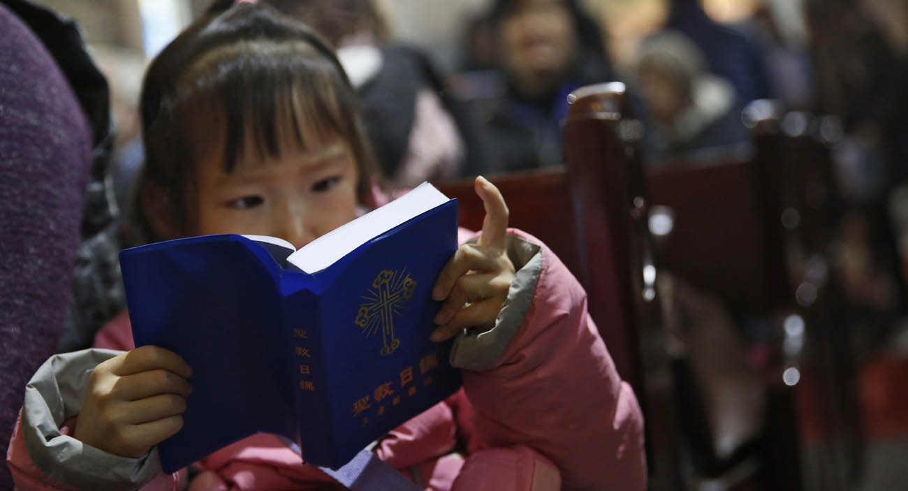 A girl looks at a Bible during Mass in 2016 at a Beijing cathedral. As young people move to cities, Catholic grandparents in rural areas are passing on the faith to their grandchildren. (CNS photo/How Hwee Young, EPA)