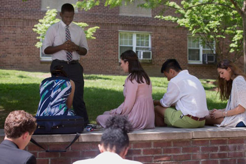 Catholic University of America student Isaiah Burroughs leads a prayer on the Washington campus April 30 with members of the Rite of Christian Initiation of Adults group he helped guide on their path to Catholicism. (CNS photo/Chaz Muth)