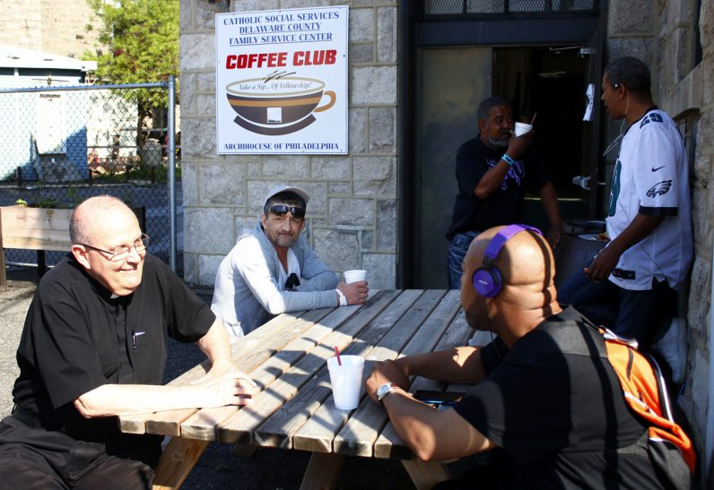 Father Anthony Orth volunteers as chaplain to the Coffee Club. Here he chats with some of the guests outside in the garden.
