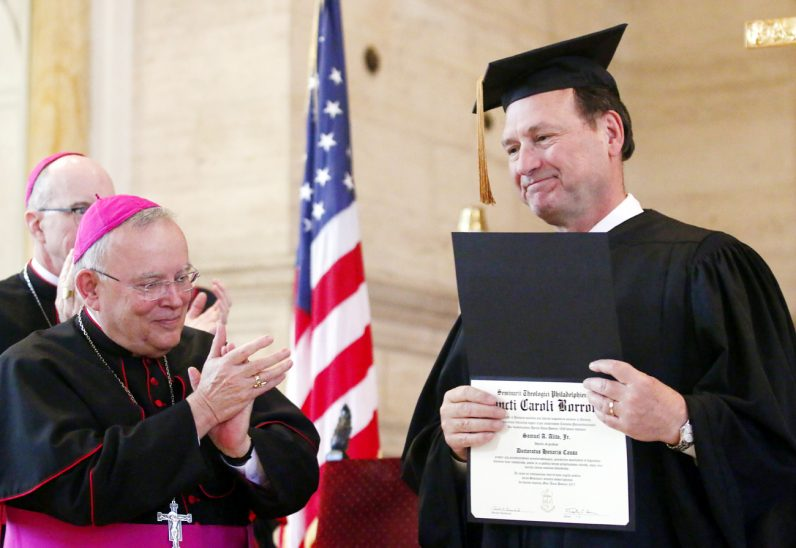 Bishop Timothy Senior (left) and Archbishop Charles Chaput applaud Justice Samuel Alito Jr. as he is presented with an honorary degree from St. Charles Borromeo Seminary.