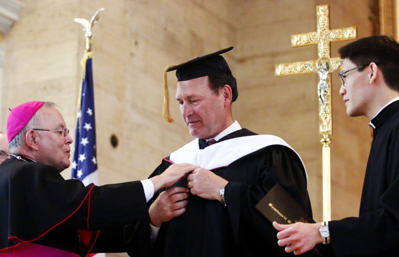 Archbishop Charles Chaput places a graduation garment on Justice Samuel Alito Jr. with the help of seminarian Anthony Raymundo.