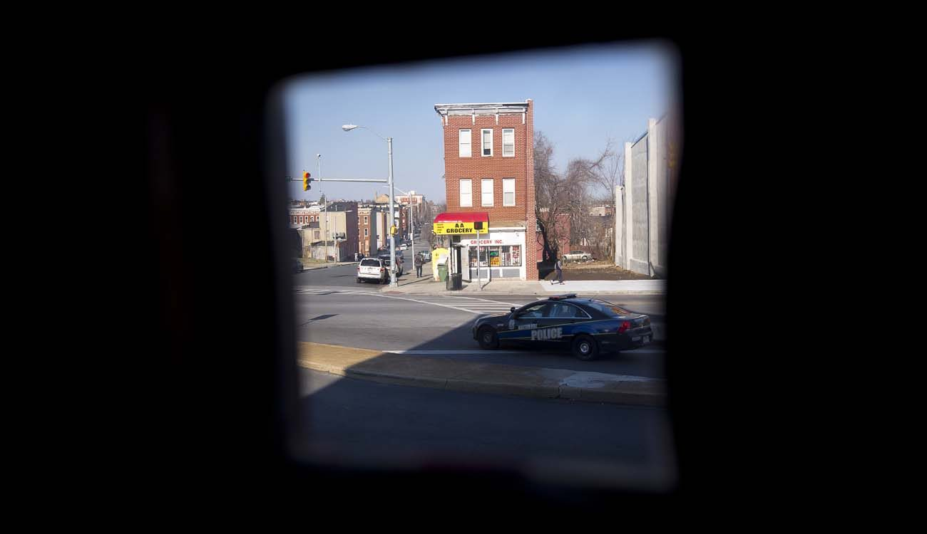 A police car is seen through the door window at St. Peter Claver Church rectory in Baltimore March 9. (CNS photo/Tyler Orsburn)