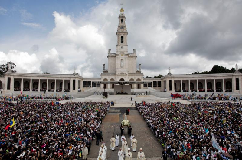 "A statue of Our Lady of Fatima is carried through a crowd in 2016 at the Marian shrine of Fatima in central Portugal, where Pope Francis plans to visit May 12-13 to celebrate the 100th anniversary of the 1917 apparitions of Mary. While tending sheep in a field, Lucia dos Santos and her two younger cousins, Francisco and Jacinta Marto, reported seeing a woman dressed all in white, ""more brilliant than the sun, shedding rays of light clearer and stronger than a crystal glass filled with the most sparkling water and pierced by the burning rays of the sun."" (CNS photo/Paulo Chunho, EPA)"