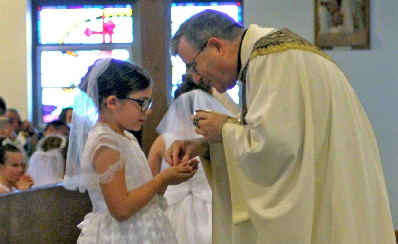 Rylee Ann Gibbons receives the Body of Christ for the first time from her pastor, Father Francis Mulranen, at Our Lady of Fatima Church, Secane, May 13.
