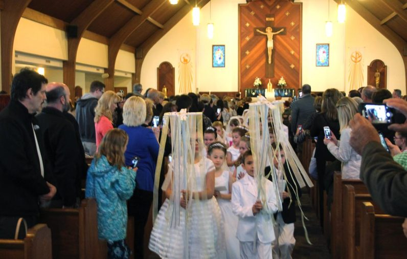 Children of Our Lady of Fatima Parish, Secane, lead the recessional at the close of Mass on Saturday, May 13, at which they received their first holy Communion.