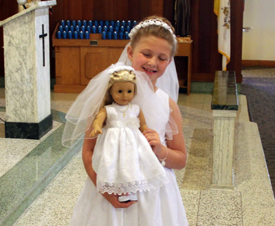 Madison Prichard is proud not only to receive first holy Communion but also of her doll Isabella, which is also wearing a communion dress given as a gift for the occasion.