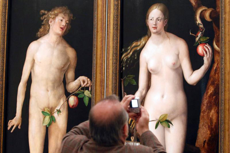 "A man takes a picture of Albrecht Durer's painting ""Adam and Eve,"" displayed at the Museo del Prado in Madrid, in this 2010 photo. In the Garden of Eden, God commanded Adam and Eve not to eat of the tree of the knowledge of good and evil. (CNS photo/Javier Lizon, EPA)"