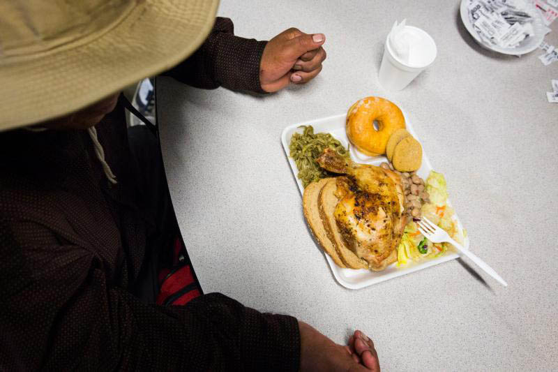 A man sits down to a meal at the St. Vincent de Paul Society dining room in Phoenix in this 2016 photo. Food connects us to our beliefs, our communities, our ancestors. (CNS photo/Nancy Wiechec) See MIDST April 20, 2017.