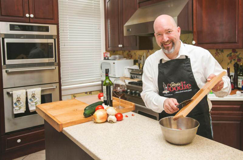 "Jeff Young, founder and producer of ""The Catholic Foodie"" blog and podcast, is pictured in this 2014 photo preparing food in the rectory kitchen at St. Stephen's Catholic Church in New Orleans. Young, whose blog mixes spiritual observations with recipes, also has a keen perspective about Catholics' relationship to food. (CNS photo/courtesy Jeff Young)"