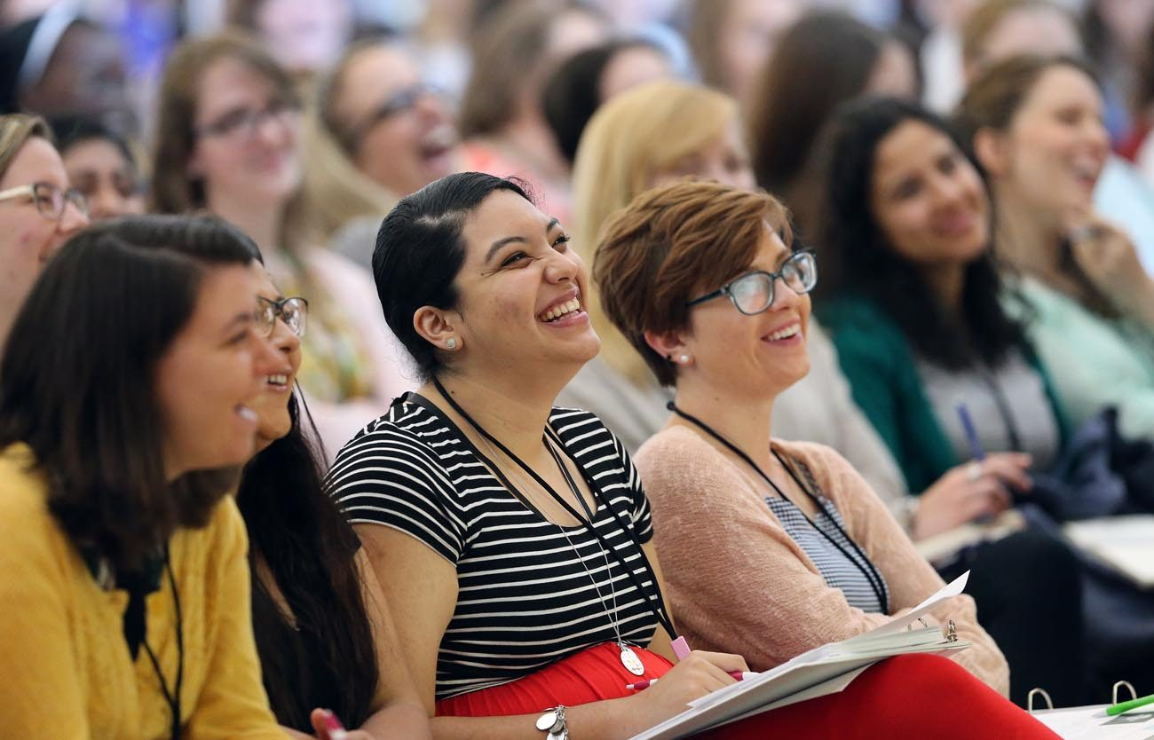 "Women laugh as they listen to a keynote speaker during a leadership forum for young Catholic women in 2016 at The Catholic University of America in Washington. In dioceses across the U.S., the 300 attendees are now implementing their ""action plans,"" new initiatives inspired by their gifts, interests and leadership skills.(CNS photo/Bob Roller)"