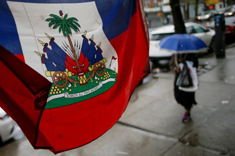 A flag from Haiti hangs outside a store as a woman walks with an umbrella May 13 in Brooklyn, N.Y. Tens of thousands of Haitians enrolled under the Temporary Protected Status program can stay in the United States until at least January. (CNS photo/Eduardo Munoz, Reuters)