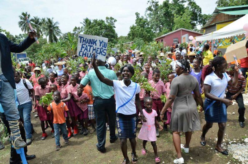 Recipients of new homes by Father Chuck's challenge in Cupelier, Haiti, show their excitement.